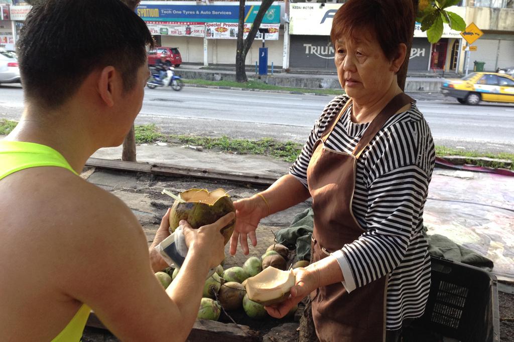 ココナッツジュースをおばちゃんから受け取る